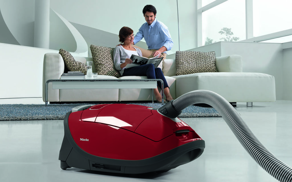 Miele vacuum with man and woman in the background