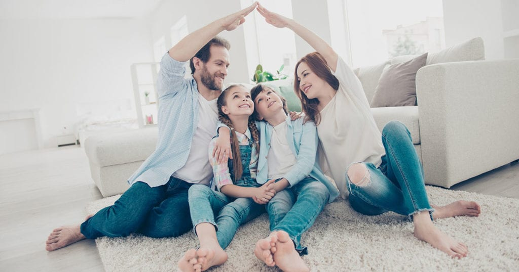 Family with two kids sitting on carpet, mom and dad making roof figure with hands arms over heads